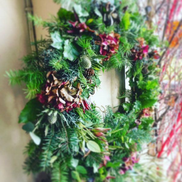 Wreath with spruce, thistles, holly leaves and hydrangea by Blue Lavender Florist London